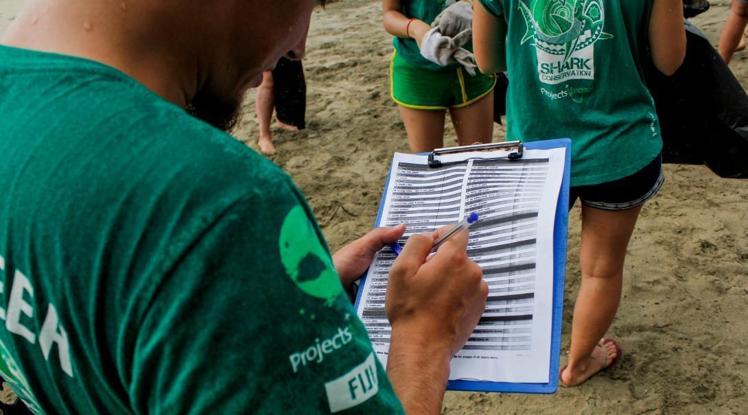 Voluntarios ambientales participan en limpieza de playas durante su voluntariado para proteger a los tiburones en Fiyi.